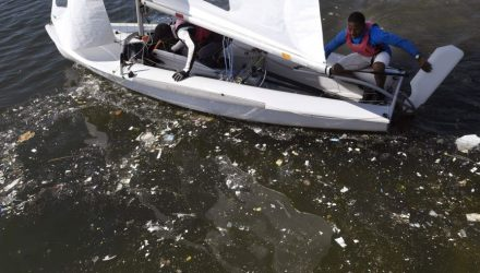 Waste litters the water as two sailors prepare for a training session at Rio de Janeiro's Guanabara Bay on August 1, 2016 ahead of the 2016 Rio Olympic Games. / AFP / WILLIAM WEST