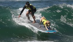 A surf dog competes in the tandem event during the 8th annual Surf City Surf Dog event at Huntington Beach, California on September 25, 2016. Dogs, big and small, and some in tandem braved the large swell that greeted them at the iconic event. / AFP PHOTO / Mark RALSTON